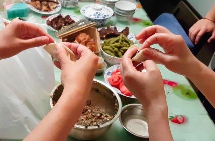 Huis Mutter zeigt Anke, wie Dumplings gefüllt und gefaltet werden.