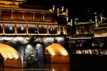 Die Häuser am Ufer des Tuo Jiang River in Fenghuang sind nachts bunt beleuchtet.