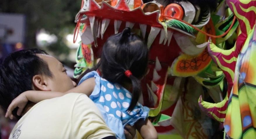 Ein junges Mädchen schaut neugierig in das Maul eines Drachenkostüms