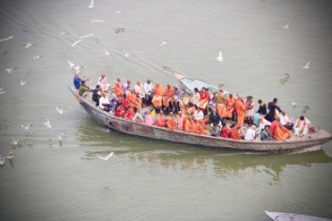 Boote fahren über den Ganges, um die Passagiere zu eine der Burning Ghats zu bringen.